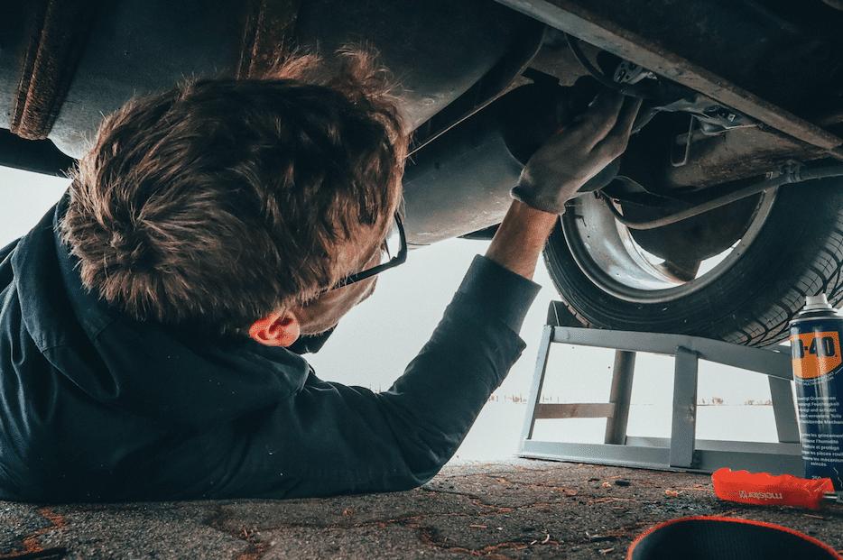 man-fixing-broken-car